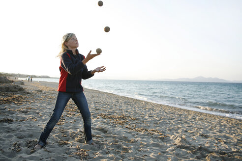 Spain, Majorca, boy juggling with three balls on the beach - TMF000086