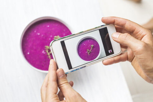 Woman taking a photo of dragon fruit smoothie with her smartphone, close-up - KNTF000206