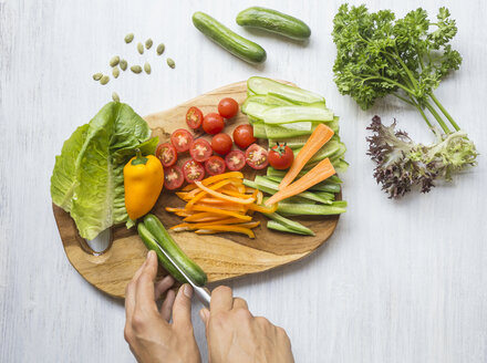 Woman's hands chopping vegetables on wooden board - KNTF000212