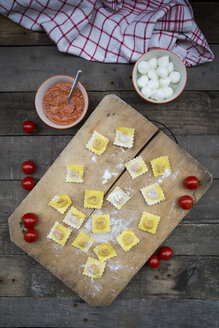Homemade noodles, ravioli, filled with tomato mozzarella on chopping board - LVF004310