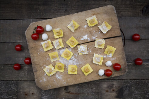 Homemade noodles, ravioli, filled with tomato mozzarella on chopping board - LVF004313