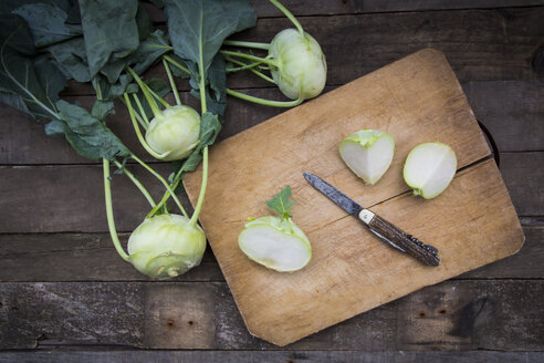 Organic kohlrabi on wood, knife on chopping board, halved - LVF004316