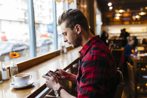 Man in a coffee shop looking at cell phone - BOYF000055