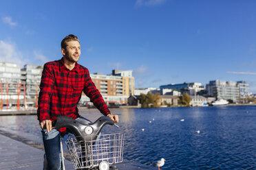 Ireland, Dublin, young man at city dock with city bike - BOYF000058