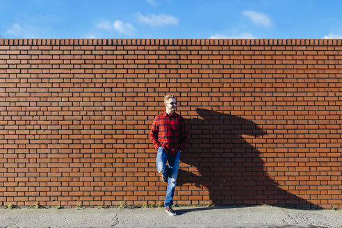 Young man leaning against brick wall - BOYF000061