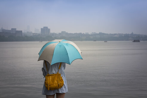 China, Zhejiang, Hangzhou, Women with umbrella looking over the West lake - NK000421