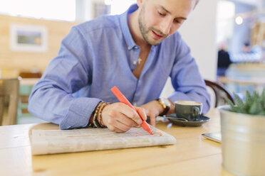 Man sitting in a coffee shop marking something in a newspaper - BOYF000075