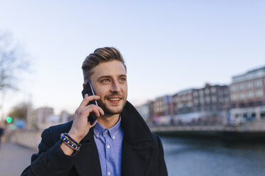 Ireland, Dublin, portrait of young businessman telephoning with smartphone - BOYF000078