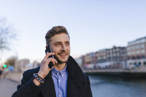 Ireland, Dublin, portrait of young businessman telephoning with smartphone - BOYF000078