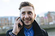 Ireland, Dublin, portrait of smiling young businessman telephoning with smartphone - BOYF000081
