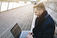 Young man sitting on a bench working with laptop - BOYF000084