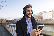 Ireland, Dublin, young man holding smartphone hearing music with headphones - BOYF000087
