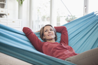 Smiling woman at home lying in hammock - RBF003570