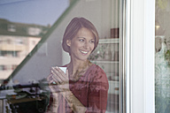 Smiling woman holding cup looking out of window - RBF003573