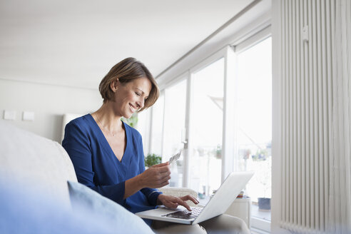 Smiling woman at home shopping online - RBF003585