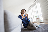 Relaxed woman at home leaning at couch - RBF003594