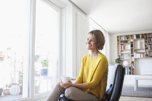 Relaxed woman at home sitting on leather chair - RBF003597