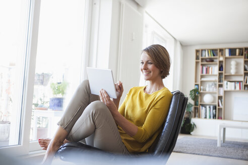 Relaxed woman at home sitting on leather chair using digital tablet - RBF003600