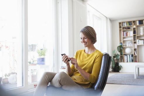 Relaxed woman at home sitting on leather chair using cell phone - RBF003603