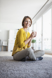 Relaxed woman at home sitting on floor holding cup - RBF003615