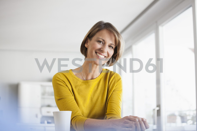 Portrait of relaxed woman at home with cup of coffee - RBF003621 - Rainer Berg/Westend61