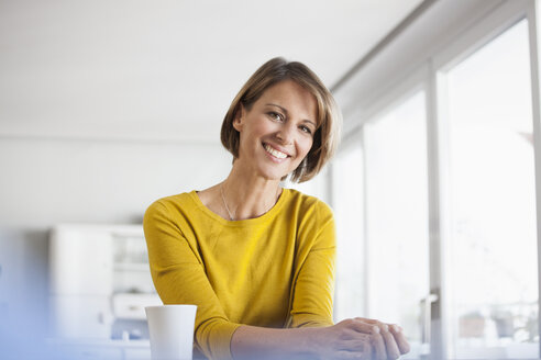 Portrait of relaxed woman at home with cup of coffee - RBF003621
