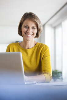 Portrait of smiling woman at home using laptop - RBF003624