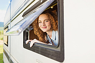 Portrit of smiling young woman  looking through window of caravan - HAPF000040