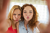 Portrait of two female friends pouting mouths while looking at camera - HAPF000046