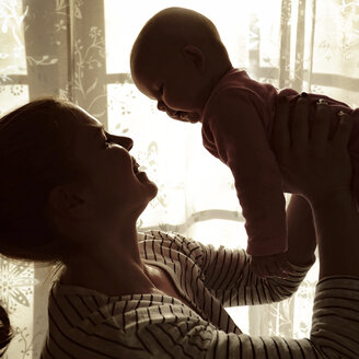 Mother holding her baby up in the air in front of a window - HOHF001384