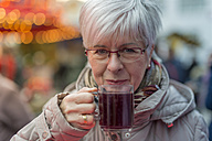 Senior woman holding glass of mulled wine - FRF000369