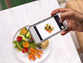 Woman taking a photo of dish with vegetables and quinoa, close-up - KNTF000218