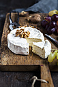 Wooden board with sliced camembert, walnuts and grapes - SBDF002574