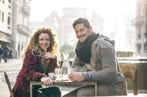 Italy, Milan, portrait of happy couple sitting at sidewalk cafe - OIPF000010