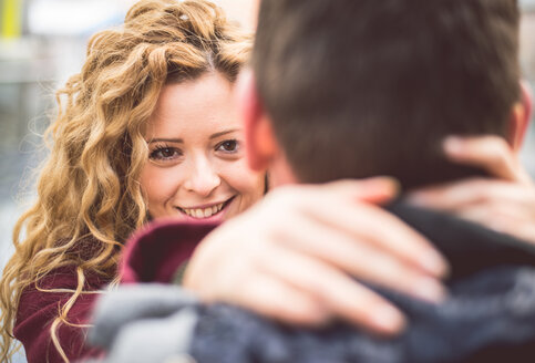 Portrait of smiling young woman hugging her boyfriend while looking at camera - OIPF000013