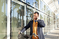 Spain, Barcelona, portrait of businessman with bicycle telephoning with smartphone - VABF000001