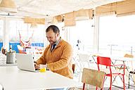 Spain, Barcelona, smiling businessman sitting at seaside cafe  using laptop - VABF000007