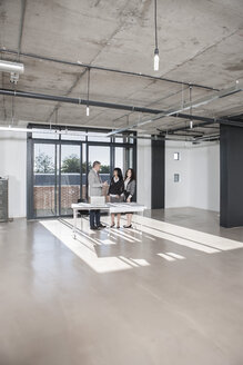 Businesspeople standing and talking in new open office - ZEF007537