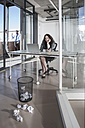 Businesswoman sitting at desk looking at laptop - ZEF007561