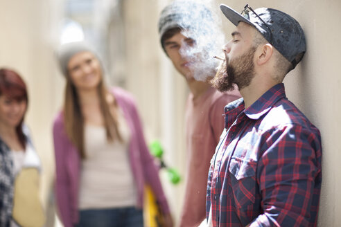 Young man smoking a cigarette with friends in background - ZEF007582