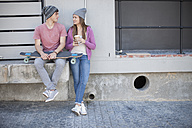 Young man with skateboard and teenage girl sitting outdoors - ZEF007603