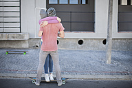 Young couple with skateboard hugging on the street - ZEF007609