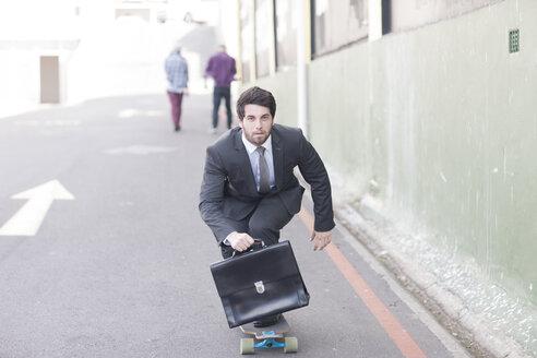 Businessman on skateboard riding down the street - ZEF007624