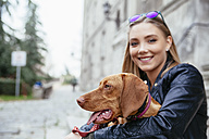 Serbia, Petrovaradin, smiling young woman holding dog in her arms - ZEDF000031