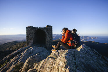 Spain, Catalunya, Girona, female hiker resting on mountaintop looking at view - EBSF001165
