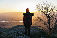 Spain, Catalunya, Girona, female hiker in the nature looking at view at sunrise - EBSF001168