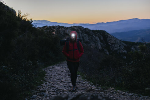 Spain, Catalunya, Girona, female hiker walking with headlamp at twilight - EBSF001174