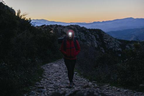 Spain, Catalunya, Girona, female hiker walking with headlamp at twilight - EBSF001174