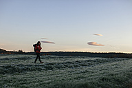 Spain, Catalunya, Girona, female hiker walking on field in the morning - EBSF001177