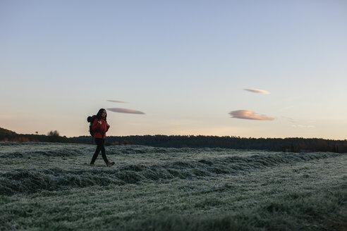 Spain, Catalunya, Girona, female hiker walking on field in the morning - EBSF001177